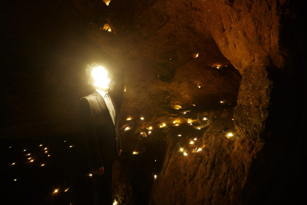 A man with a face made of lights stands in a cave which contains lots of tiny lights stands in Redcliffe Caves
