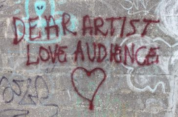 A concrete wall with 'Dear Artist Love Audience' written in dark read spray paint with a heart underneath.
