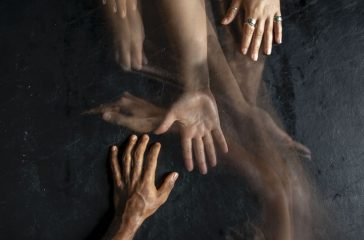 A timelapse photo of hands reaching out to each other across a black background