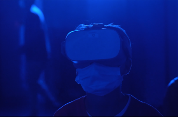 A close up photograph of a man wearing vr headset goggles and a face mask. The lighting is dark blue.