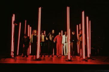 Lots of artists standing in a dark room. The floor and beams are lit with a red light, the artists are standing next to the beams.
